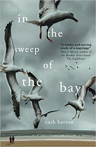 Image shows the book cover of In The Sweep of the Bay by Cath Barton. An atmospheric cover, filled with dark cloudy sky, with two people featuring small in the beach scene below with seagull dominating the fore of the image.